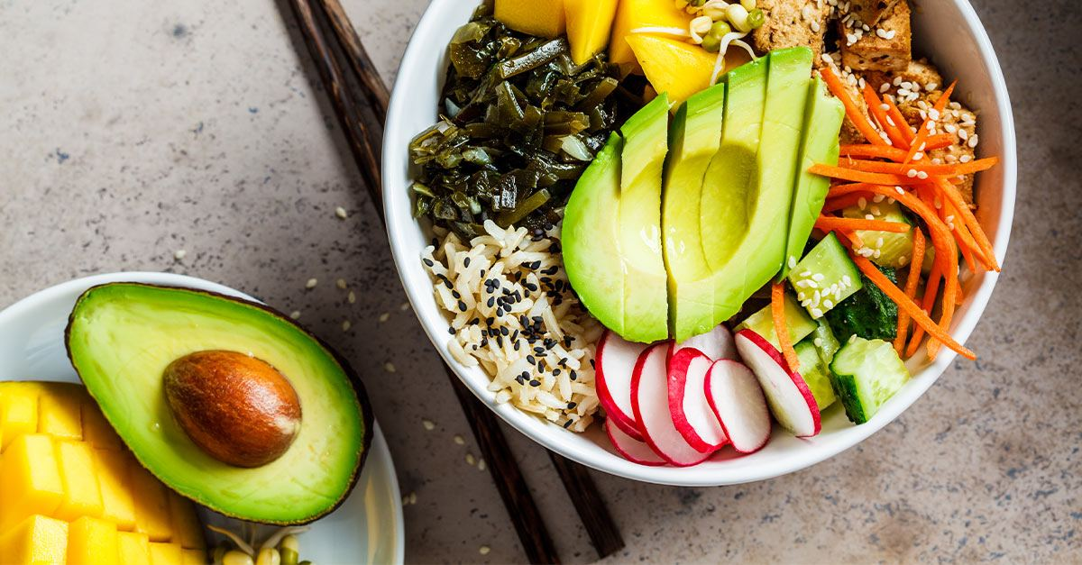 Bowl of cut up healthy vegetables and fruits.