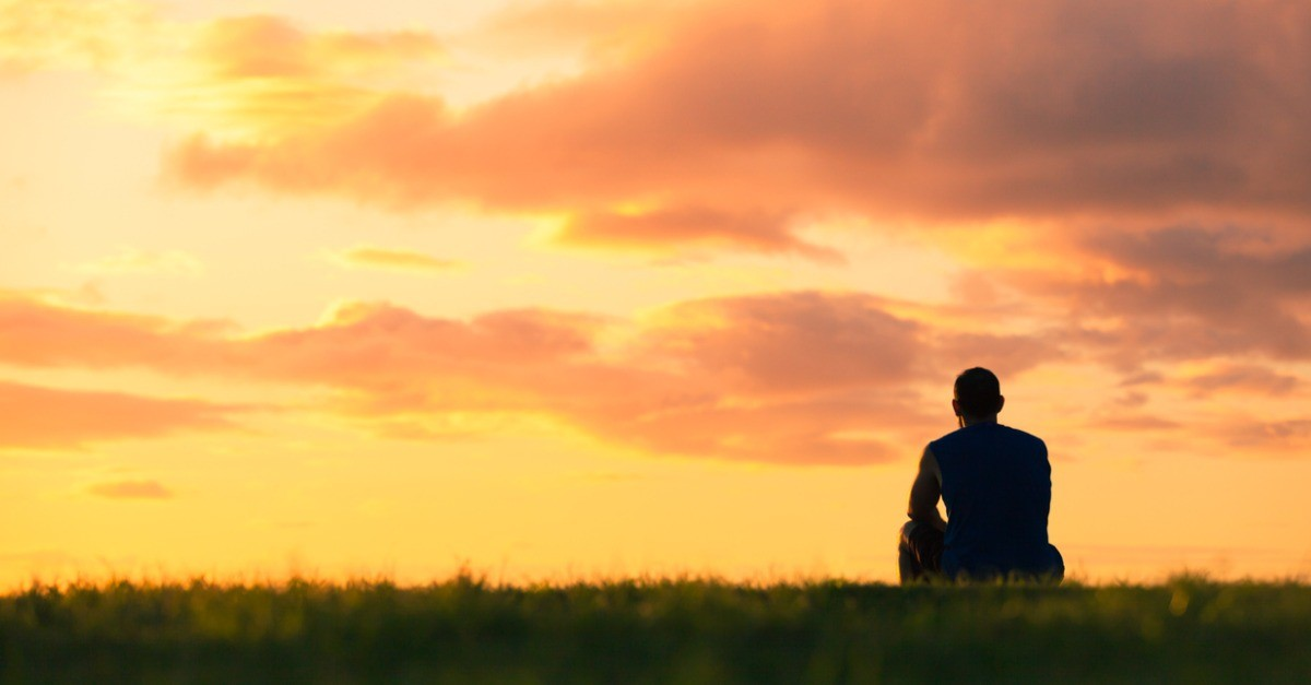 Silhouette of a man sitting on the grass during a sunset.
