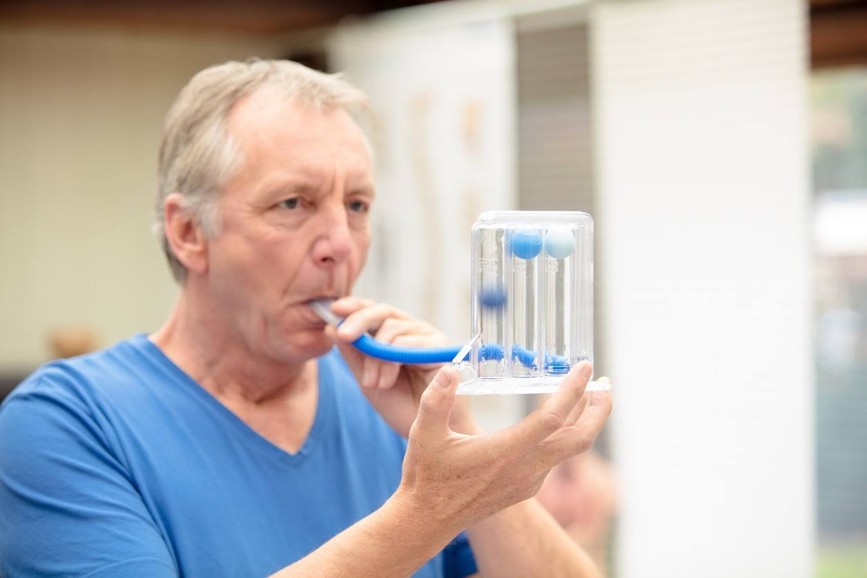 Mature man, performing a simple lung function test by using a triflow
