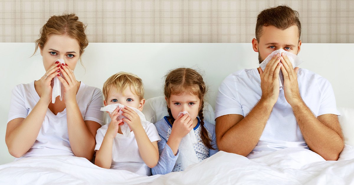 Family in bed, suffering from allergies.