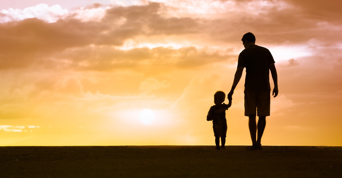 Silhouette of a father in son walking together in front of a beautiful sunset